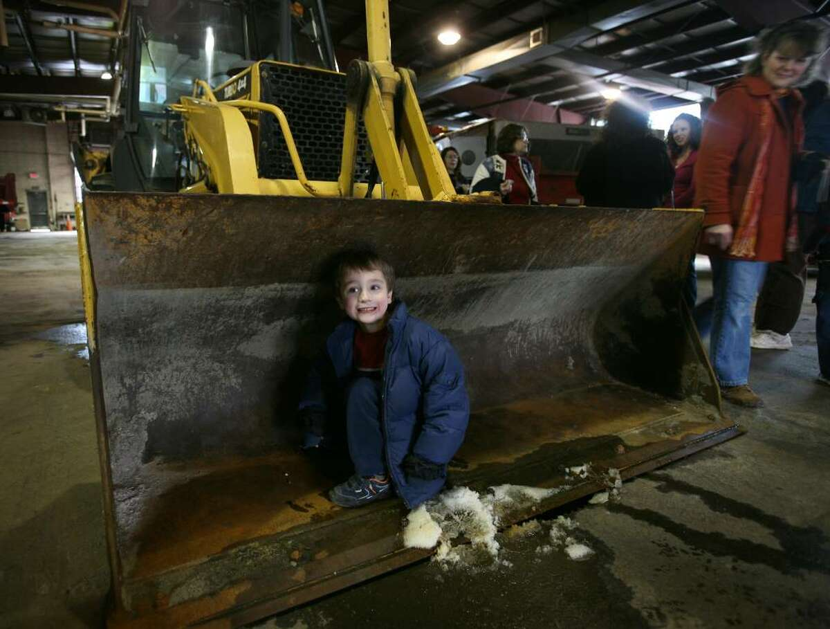 Evan Shail, 6 of Seymour, sits in the front scoop of a backhoe during a visit of homeschooled children to the Seymour Public Works Department on Wednesday, January 13, 2010 in Seymour, Conn.