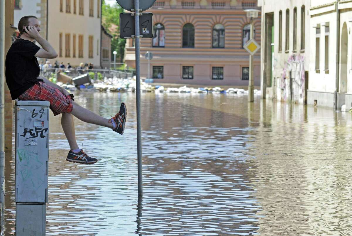 A man talks on his cellphone as he sits on a power distribution station in an area flooded by river Saale in Halle, central Germany, Wednesday, June 5, 2013. Heavy rainfalls cause flooding along rivers and lakes in Germany, Austria, Switzerland, the Czech Republic and Hungary.