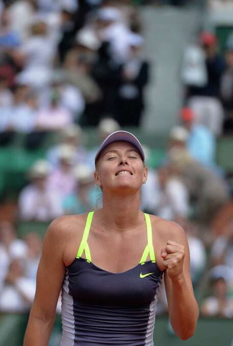TOPSHOTS Russia's Maria Sharapova celebrates after winning against Serbia's Jelena Jankovic during a French tennis Open quarter final match at the Roland Garros stadium in Paris on June 5, 2013.     AFP PHOTO / MIGUEL MEDINAMIGUEL MEDINA/AFP/Getty Images Photo: MIGUEL MEDINA, AFP/Getty Images / AFP