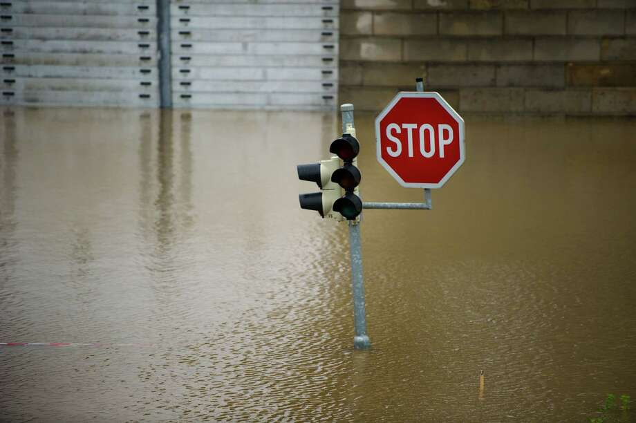 TOPSHOTS A traffic light and a sign stand on an overflooded street in Dresden, eastern Germany, on June 4, 2013.Torrential rain and heavy flooding hit central Europe. AFP PHOTO / ARNO BURGI   GERMANY OUTARNO BURGI/AFP/Getty Images Photo: ARNO BURGI, AFP/Getty Images / DPA