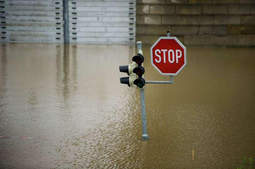TOPSHOTS A traffic light and a sign stand on an overflooded street in Dresden, eastern Germany, on J