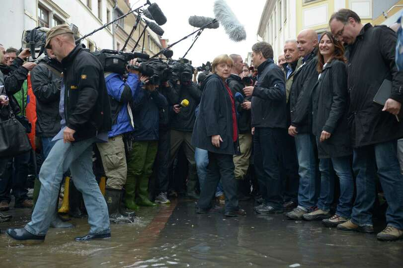 TOPSHOTS German Chancellor Angela Merkel speaks with rescue helpers and residents as she visits the