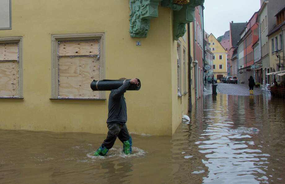 TOPSHOTS A man walks through a street submerging in the floods of the river Elbe in Pirna, eastern Germany, on June 4, 2013. German Chancellor Angela Merkel pledged 100 million euros ($130 million) in emergency aid for flood-ravaged areas, as surging waters that have already claimed 10 lives and forced tens of thousands of evacuations across Europe bore down towards Germany.    AFP PHOTO / JOHANNES EISELEJOHANNES EISELE/AFP/Getty Images Photo: JOHANNES EISELE, AFP/Getty Images / AFP