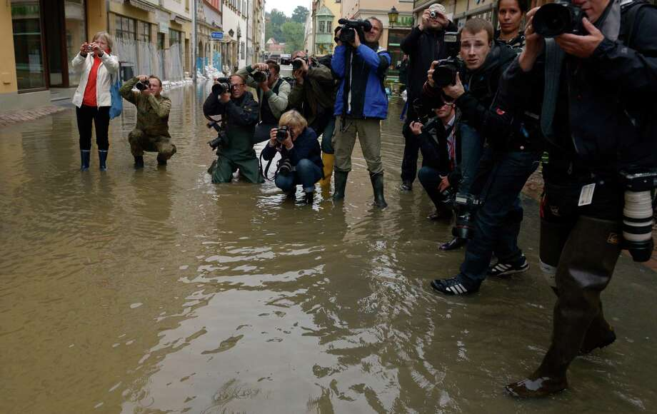 TOPSHOTS Photographers and cameramen stand in a street submerging in the floods of the river Elbe in Pirna, eastern Germany, to take pictures of the German Chancellor during her visit on June 4, 2013. German Chancellor Angela Merkel pledged 100 million euros ($130 million) in emergency aid for flood-ravaged areas, as surging waters that have already claimed 10 lives and forced tens of thousands of evacuations across Europe bore down towards Germany.    AFP PHOTO / JOHANNES EISELEJOHANNES EISELE/AFP/Getty Images Photo: JOHANNES EISELE, AFP/Getty Images / AFP