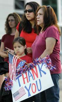 Gabbie Bode, 5, waits with her mother, Nichole Bode, left, and grandmother, Yolanda Cruz, right, to see firefighters march along Kirby to a memorial service honoring four Houston firefighters at Reliant Stadium Wednesday, June 5, 2013 in Houston. Firefighters from Station 51 Robert Bebee and Capt. Matthew Renaud and from Station 68 Anne Sullivan and Robert Garner were killed and 13 others were injured when the roof of the burning Southwest Inn in the 5800 block of the Southwest Freeway collapsed last Friday. Photo: Melissa Phillip, Houston Chronicle / © 2013  Houston Chronicle