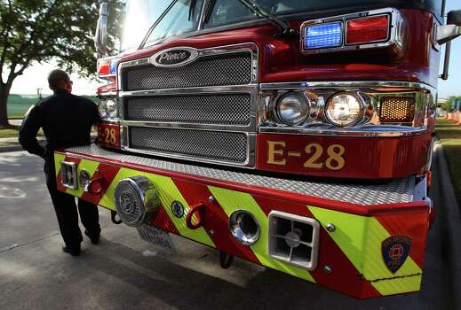 A member of the San Antonio Fire Department stands next to his truck lined up along Kirby before a memorial service honoring Houston firefighters Robert Bebee, Robert Garner, Matthew Renaud, and Anne Sullivan at Reliant Stadium Wednesday, June 5, 2013, in Houston. The four firefighters died in a 5-alarm fire while searching for people they thought might be trapped inside a burning motel and restaurant last Friday. Photo: Karen Warren, Houston Chronicle / © 2013  Houston Chronicle
