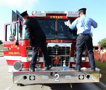 Members of the Bryan Fire Department clean the windshield of their truck lined up along Kirby before a memorial service honoring Houston firefighters Robert Bebee, Robert Garner, Matthew Renaud, and Anne Sullivan at Reliant Stadium Wednesday, June 5, 2013, in Houston. The four firefighters died in a 5-alarm fire while searching for people they thought might be trapped inside a burning motel and restaurant last Friday. Photo: Karen Warren, Houston Chronicle / © 2013  Houston Chronicle