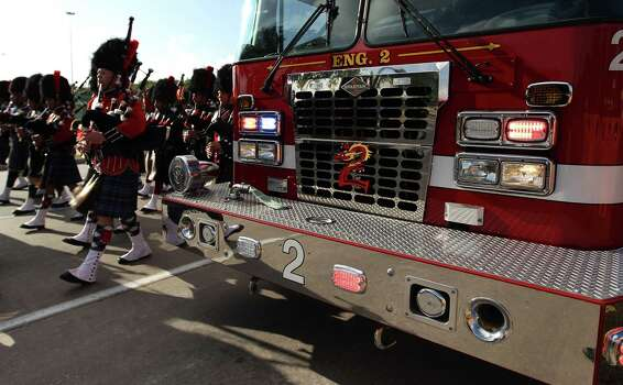 Members of the pipe and drum corps march past Bryan Fire Department's truck lined up along Kirby during the procession to Reliant Stadium during a memorial service honoring Houston firefighters Robert Bebee, Robert Garner, Matthew Renaud, and Anne Sullivan at Reliant Stadium Wednesday, June 5, 2013, in Houston. The four firefighters died in a 5-alarm fire while searching for people they thought might be trapped inside a burning motel and restaurant last Friday. Photo: Karen Warren, Houston Chronicle / © 2013  Houston Chronicle