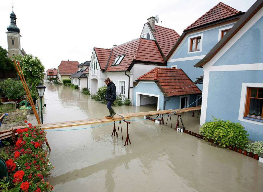 TOPSHOTS  A women crosses a makeshift bridge over overflooded streets in Unterloiben, Austria on June 4, 2013. Torrential rain and heavy flooding hit central Europe. AFP PHOTO / DIETER NAGLDIETER NAGL/AFP/Getty Images Photo: DIETER NAGL, AFP/Getty Images / AFP