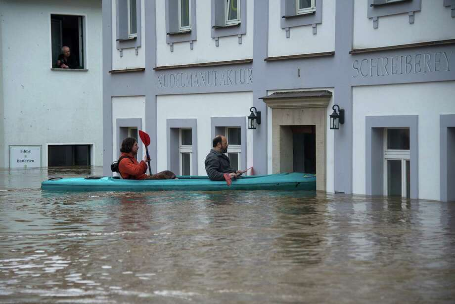 TOPSHOTS People canoe in the flooded city of Wehlen, in eastern Germany,  on June 4, 2013. Torrential rain and heavy flooding hit central Europe. AFP PHOTO / JOHANNES EISELEJOHANNES EISELE/AFP/Getty Images Photo: JOHANNES EISELE, AFP/Getty Images / AFP