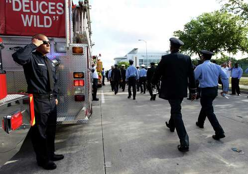 Members of the Houston Fire Department march up Kirby towards Reliant Stadium as they are saluted by firefighters from other cities during a memorial service honoring Houston firefighters Robert Bebee, Robert Garner, Matthew Renaud, and Anne Sullivan at Reliant Stadium Wednesday, June 5, 2013, in Houston. The four firefighters died in a 5-alarm fire while searching for people they thought might be trapped inside a burning motel and restaurant last Friday. Photo: Karen Warren, Houston Chronicle / © 2013  Houston Chronicle