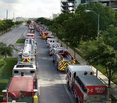 Fire trucks line up Kirby during the procession  leading to a memorial service honoring Houston firefighters Robert Bebee, Robert Garner, Matthew Renaud, and Anne Sullivan at Reliant Stadium Wednesday, June 5, 2013, in Houston. The four firefighters died in a 5-alarm fire while searching for people they thought might be trapped inside a burning motel and restaurant last Friday. Photo: Karen Warren, Houston Chronicle / © 2013  Houston Chronicle