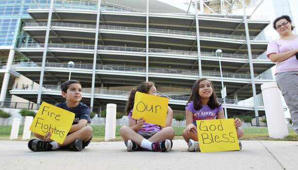 "Adam Rodriguez, 5, with his sisters, Ava, 8, center, and Grace, 9, right, hold signs that say ""God Bless our Firefighters"" as they watch a procession along Kirby during a memorial service honoring Houston firefighters Robert Bebee, Robert Garner, Matthew Renaud, and Anne Sullivan at Reliant Stadium Wednesday, June 5, 2013, in Houston. The four firefighters died in a 5-alarm fire while searching for people they thought might be trapped inside a burning motel and restaurant last Friday. Photo: Karen Warren, Houston Chronicle / © 2013  Houston Chronicle"