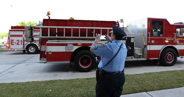 A Houston Police Officer takes a photo of fire trucks line up Kirby during the procession  leading to a memorial service honoring Houston firefighters Robert Bebee, Robert Garner, Matthew Renaud, and Anne Sullivan at Reliant Stadium Wednesday, June 5, 2013, in Houston. The four firefighters died in a 5-alarm fire while searching for people they thought might be trapped inside a burning motel and restaurant last Friday. Photo: Karen Warren, Houston Chronicle / © 2013  Houston Chronicle
