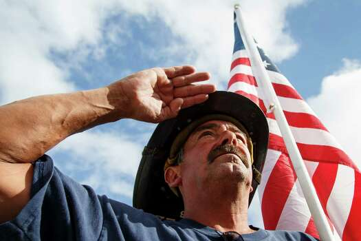 Mickey Lopez, a retired firefighter from Chicago, salutes during a memorial service honoring four Houston firefighters at Reliant Stadium Wednesday, June 5, 2013. In Houston. Four firefighters died when a part of a building collapsed on them while they were searching for people they thought might be trapped inside a burning motel and restaurant last Friday. Photo: Michael Paulsen, Houston Chronicle / © 2013 Houston Chronicle