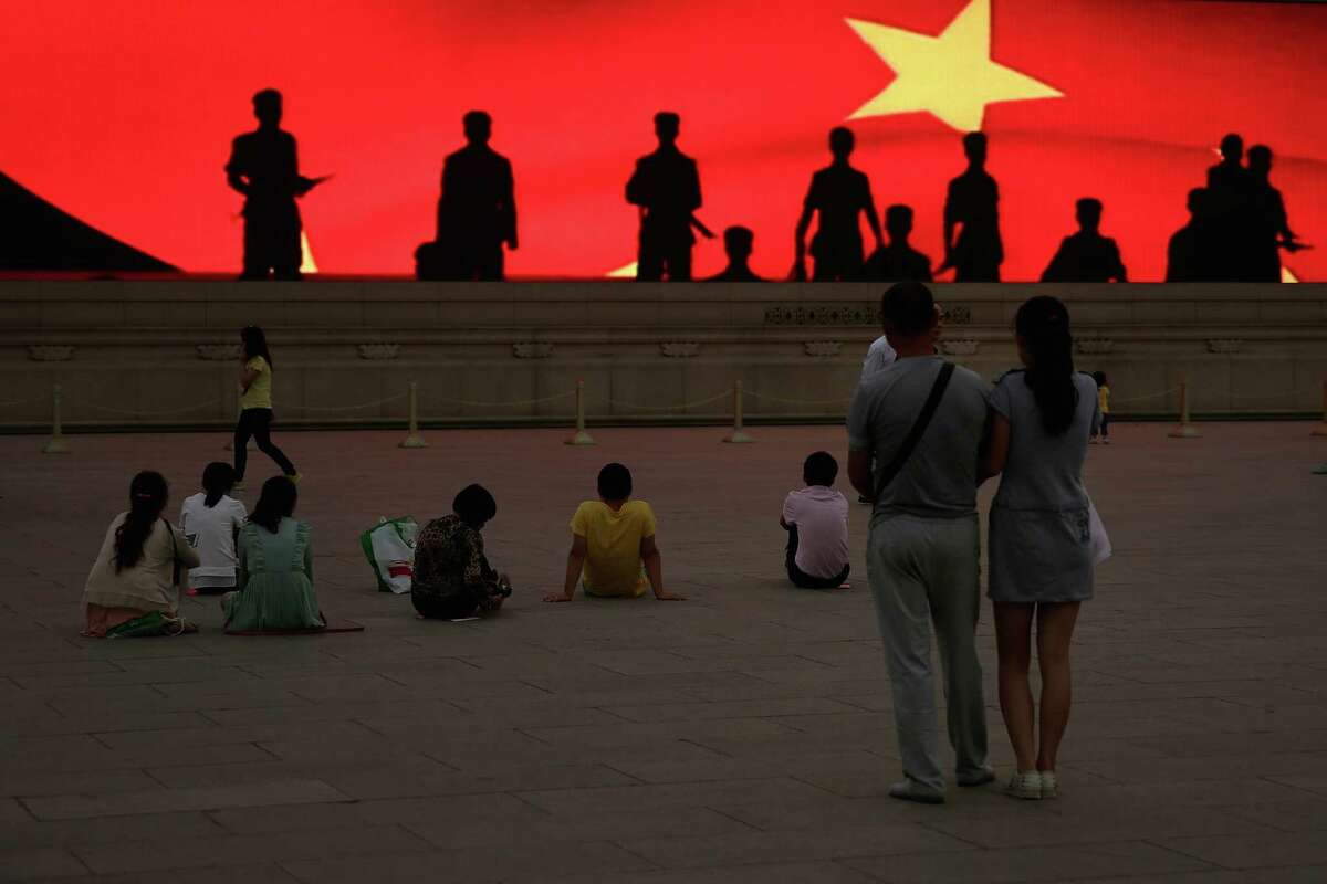 BEIJING, CHINA - JUNE 04: Chinese tourists watch a LED screen showing soldiers' shadow before the customary ceremony of lowering flag at Tiananmen Square on June 4, 2013 in Beijing, China.
