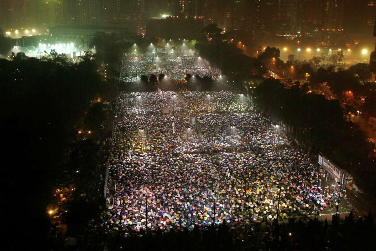Tens of thousands of people attend a candlelight vigil in heavy rain at Victoria Park in Hong Kong Tuesday, June 4, 2013 to mark the 24th anniversary of the June 4th Chinese military crackdown on the pro-democracy movement in Beijing.