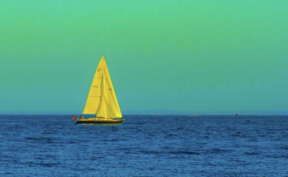 SUNDAY EVENING SAIL A sailboat passing Compo Beach is outlined against a pale, Sunday evening sky. The soothing scene marking the end of the weekend was captured by Dayle Brownstein. Photo: Contributed Photo / Fairfield Citizen contributed