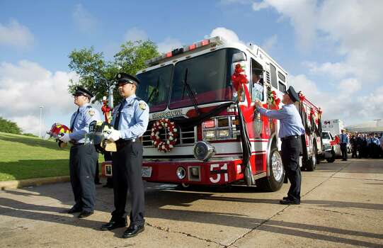 David Eckerman, left, and Joel Rincon, both fire fighters with Station 51, take their place with helmets representing fallen fire fighters  Robert Bebee and Matthew Renauda memorial service also honoring , Robert Garner, , and Anne Sullivan at Reliant Stadium Wednesday, June 5, 2013, in Houston. The four firefighters died in a 5-alarm fire while searching for people they thought might be trapped inside a burning motel and restaurant last Friday. Photo: Brett Coomer, Houston Chronicle / © 2013  Houston Chronicle