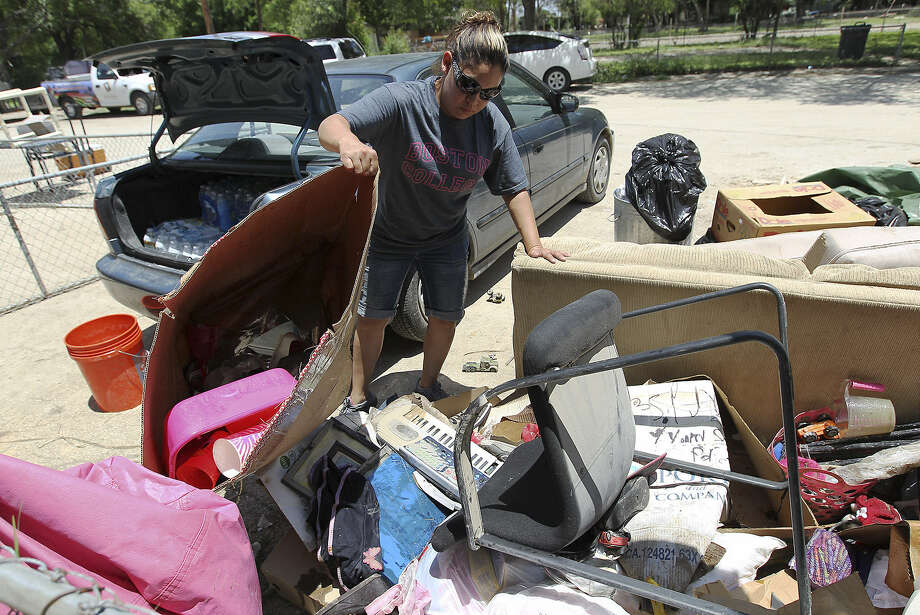Norma Sifuentes tosses out items damaged from Memorial Day weekend flooding at Big Tree Trailer City. Photo: Kin Man Hui / San Antonio Express-News