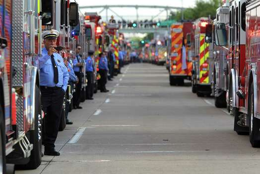 A firefighter takes a photo of other fire engines in the procession during a memorial service honoring Houston firefighters Robert Bebee, Robert Garner, Matthew Renaud, and Anne Sullivan at Reliant Stadium Wednesday, June 5, 2013, in Houston. The four firefighters died in a 5-alarm fire while searching for people they thought might be trapped inside a burning motel and restaurant last Friday. Photo: Karen Warren, Houston Chronicle / © 2013  Houston Chronicle