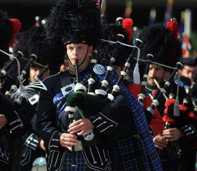 Members of the bagpipe corps play as they march toward Reliant Stadium during a memorial service honoring Houston firefighters Robert Bebee, Robert Garner, Matthew Renaud, and Anne Sullivan at Reliant Stadium Wednesday, June 5, 2013, in Houston. The four firefighters died in a 5-alarm fire while searching for people they thought might be trapped inside a burning motel and restaurant last Friday. Photo: Karen Warren, Houston Chronicle / © 2013  Houston Chronicle