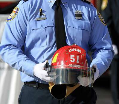 A firefighter carries a helmet from Station 51 during the procession up Kirby during a memorial service honoring Houston firefighters Robert Bebee, Robert Garner, Matthew Renaud, and Anne Sullivan at Reliant Stadium Wednesday, June 5, 2013, in Houston. The four firefighters died in a 5-alarm fire while searching for people they thought might be trapped inside a burning motel and restaurant last Friday. Photo: Karen Warren, Houston Chronicle / © 2013  Houston Chronicle