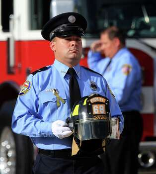 A firefighter carries a helmet from Station 68 during the procession up Kirby during a memorial service honoring Houston firefighters Robert Bebee, Robert Garner, Matthew Renaud, and Anne Sullivan at Reliant Stadium Wednesday, June 5, 2013, in Houston. The four firefighters died in a 5-alarm fire while searching for people they thought might be trapped inside a burning motel and restaurant last Friday. Photo: Karen Warren, Houston Chronicle / © 2013  Houston Chronicle