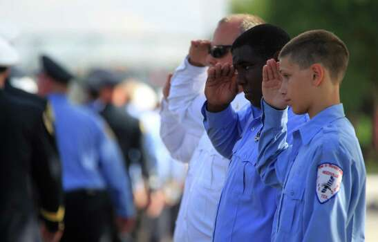Members of the Needville Volunteer Fire Department salute as the procession passes them during a memorial service honoring Houston firefighters Robert Bebee, Robert Garner, Matthew Renaud, and Anne Sullivan at Reliant Stadium Wednesday, June 5, 2013, in Houston. The four firefighters died in a 5-alarm fire while searching for people they thought might be trapped inside a burning motel and restaurant last Friday. Photo: Karen Warren, Houston Chronicle / © 2013  Houston Chronicle