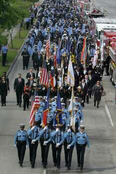Firefighters and others march along Kirby to a memorial service honoring four Houston firefighters at Reliant Stadium Wednesday, June 5, 2013 in Houston. Firefighters Robert Bebee, Anne Sullivan, Robert Garner and Capt. Matthew Renaud were killed and 13 others were injured when the roof of the burning Southwest Inn in the 5800 block of the Southwest Freeway collapsed last Friday. Photo: Melissa Phillip, Houston Chronicle / © 2013  Houston Chronicle