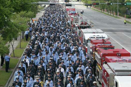 Firefighters march along Kirby to a memorial service honoring four Houston firefighters at Reliant Stadium Wednesday, June 5, 2013 in Houston. Firefighters Robert Bebee, Anne Sullivan, Robert Garner and Capt. Matthew Renaud were killed and 13 others were injured when the roof of the burning Southwest Inn in the 5800 block of the Southwest Freeway collapsed last Friday. Photo: Melissa Phillip, Houston Chronicle / © 2013  Houston Chronicle