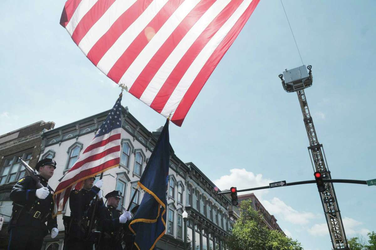 The Troy Police Department color guard marches under a large flag hanging over 4th Street as they marched in Troy Flag Day Parade on Sunday, June 10, 2012 in Troy, NY. (Paul Buckowski / Times Union)