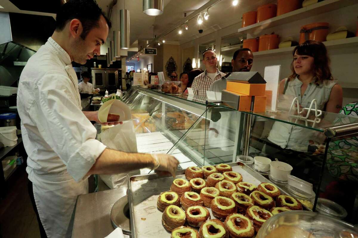 This June 3, 2013 photo shows chef Dominique Ansel, left, boxing cronuts, a croissant-donut hybrid, as customers line-up to purchase them at the Dominique Ansel Bakery in New York. Ansel makes only 200 to 250 Cronuts every morning and has been selling out within an hour.