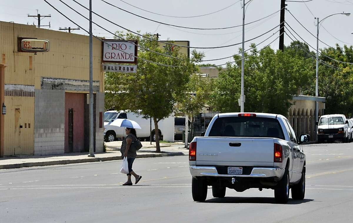 A woman crosses Lassen Avenue, May 21, 2013 in Huron, California. Huron is 98 percent Latino and the fourth-poorest place in California. (Eric Paul Zamora/Fresno Bee/MCT)