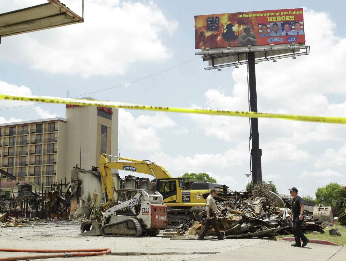 A billboard honoring the four fallen firefighters is shown as investigators continue their work at Southwest Inn, 6855 Southwest Freeway, Wednesday, June 5, 2013 where a fire killed four Houston firefighters on Friday.