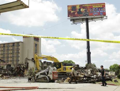 A billboard honoring the four fallen firefighters is shown as investigators continue their work at Southwest Inn, 6855 Southwest Freeway, Wednesday, June 5, 2013 where a fire killed four Houston firefighters on Friday. Photo: Houston Chronicle