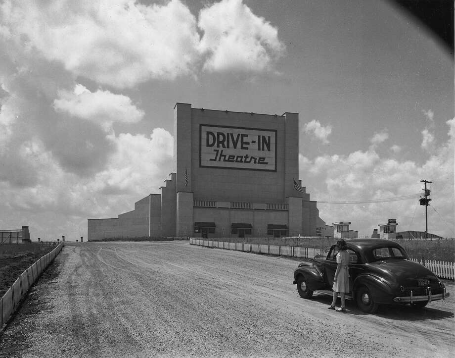 "A woman standing next to a parked car in the middle of the road, looking up at a sign that reads, ""Drive-In Theatre."" Photo: George Enell, Getty Images / Archive Photos"