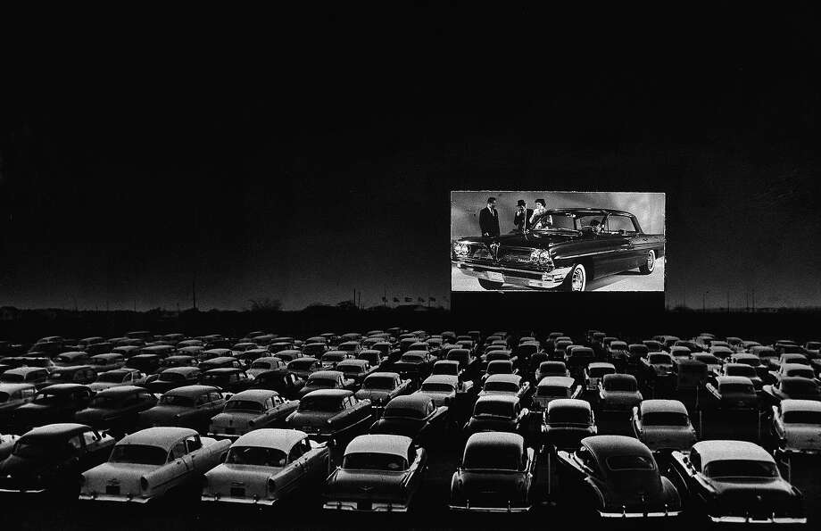 Vehicles fill a drive-in theater while people on the screen stand near a new car, 1950s. Photo: New York Times Co., Getty Images / 2004 Getty Images