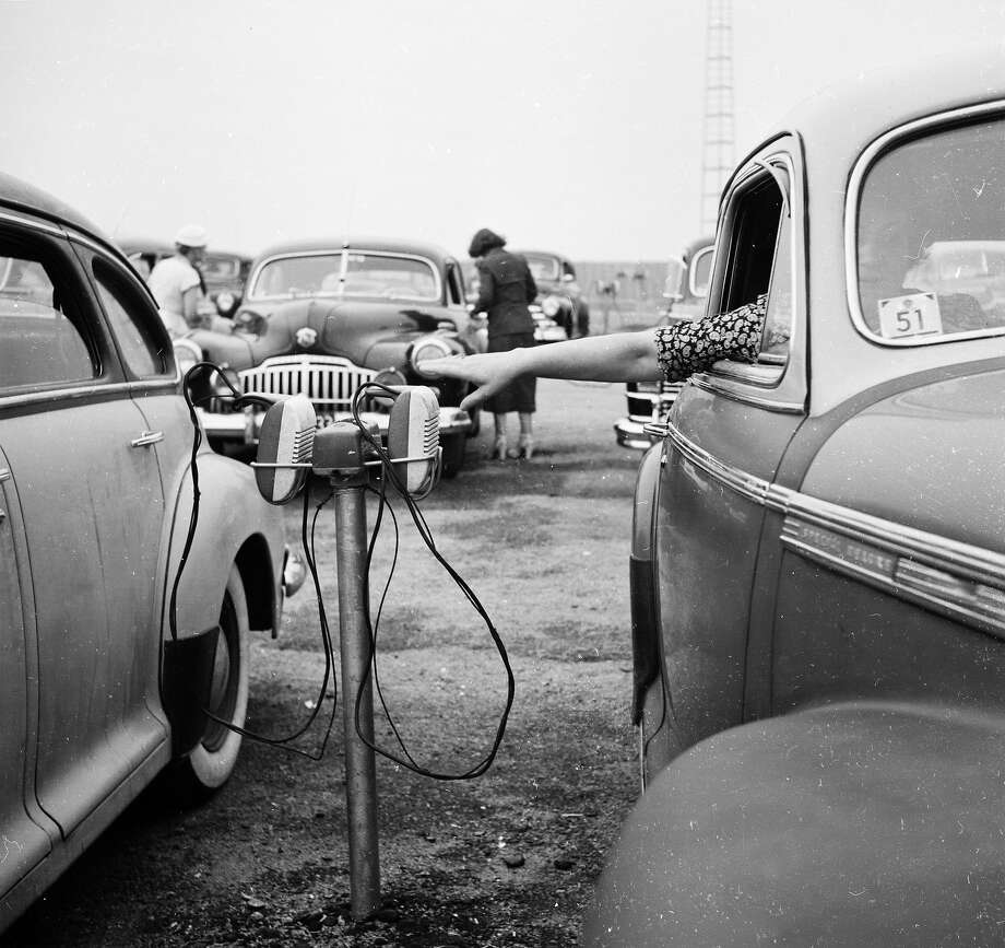 A woman reaches for a car speaker at a drive-in church in Massachusetts in 1951. Photo: Ernst Haas, Getty Images / Ernst Haas