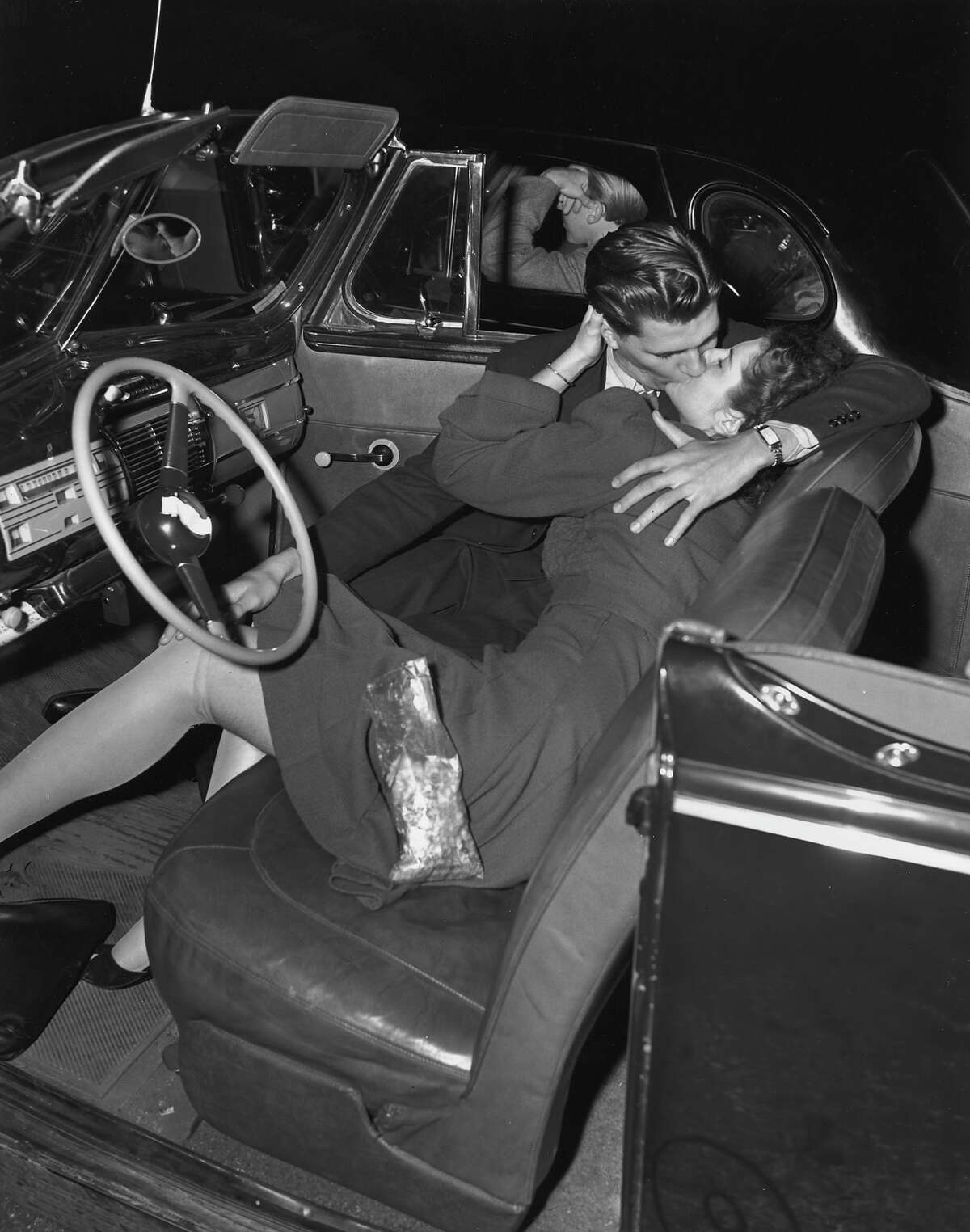 A couple kissing in the front seat of a convertible car at a drive-in movie theater, 1945.