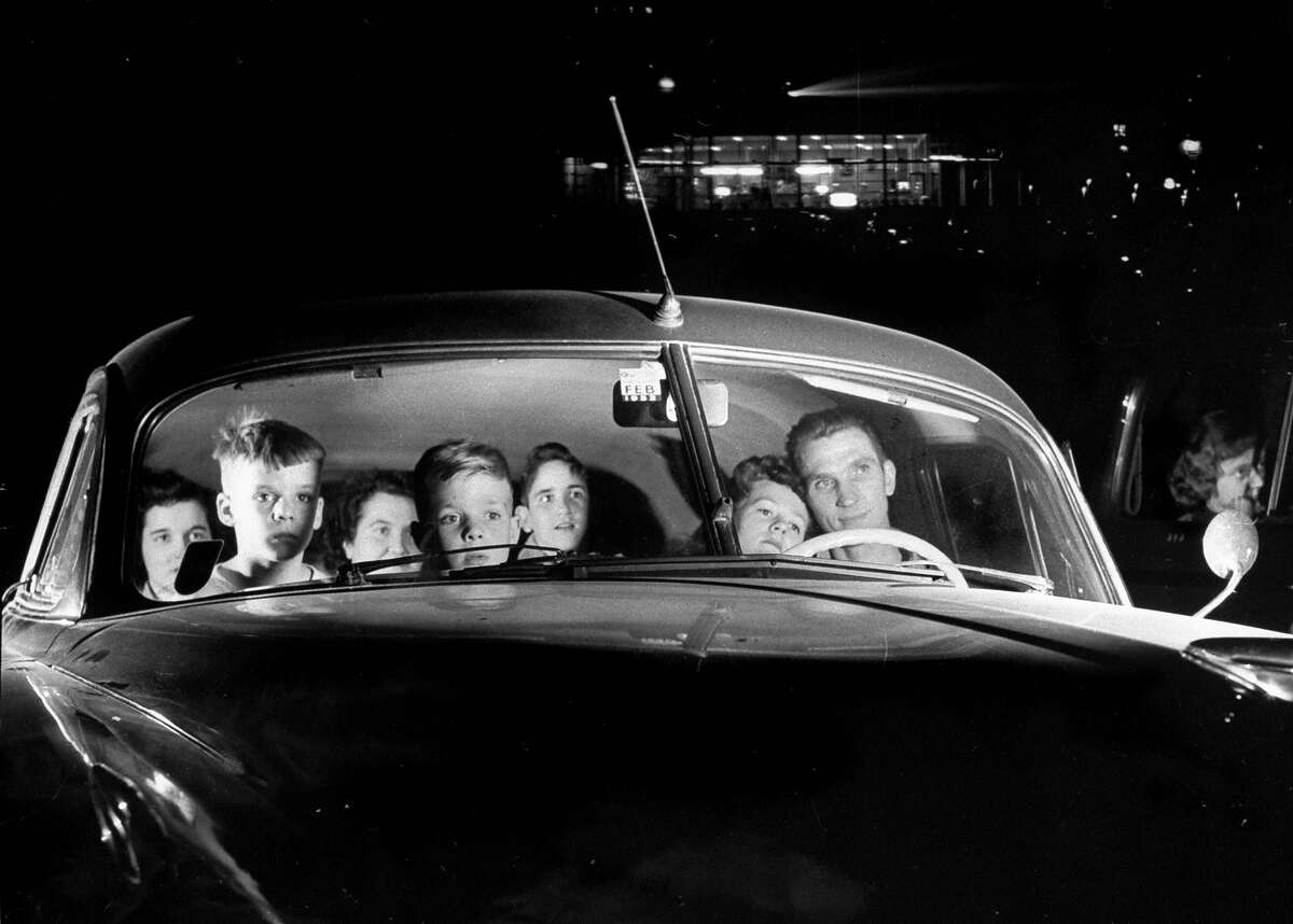 Carload of happy movie fans incl. parents w. their kids who get in free, watching show at drive-in theater.