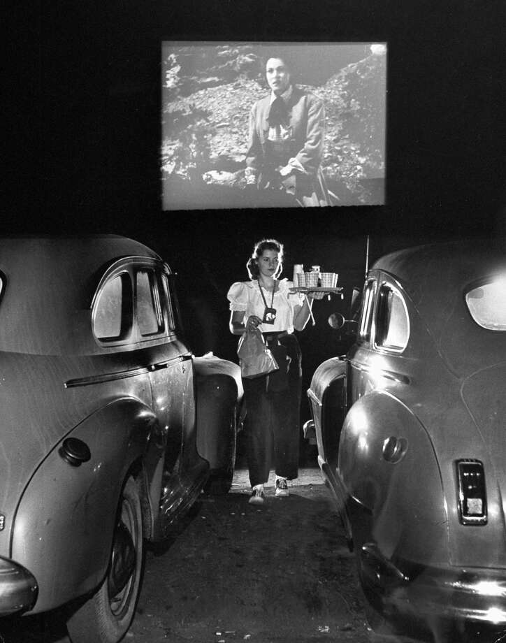 A carhop carries tray of food & drinks to car occupants at drive-in movie in 1948. Photo: Allan Grant, Time & Life Pictures/Getty Image / Time Life Pictures