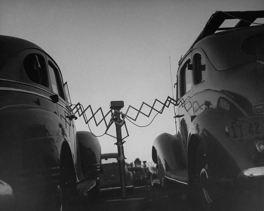 Cars parked at Rancho Drive-In Theater w. the accordion-like fulcrum arms of movie speakers reaching into each driver's front window, which they will push back onto the central post when the movie is over. Photo: Allan Grant, Time & Life Pictures/Getty Image / Time Life Pictures