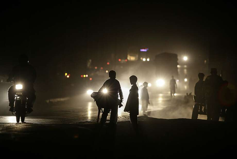 Powerless: Headlamps silhouette Pakistanis walking a darkened street on the 