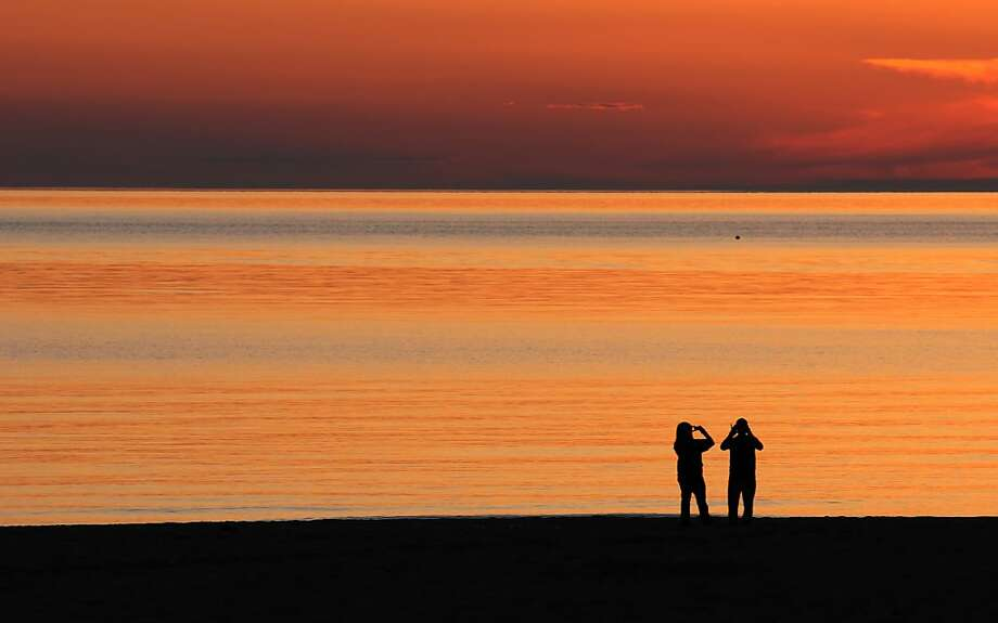 Coming to a Facebook page soon:A couple enjoy documenting a sunset on their   smartphones at Silver Beach in St. Joseph, Mich. Photo: Don Campbell, Associated Press