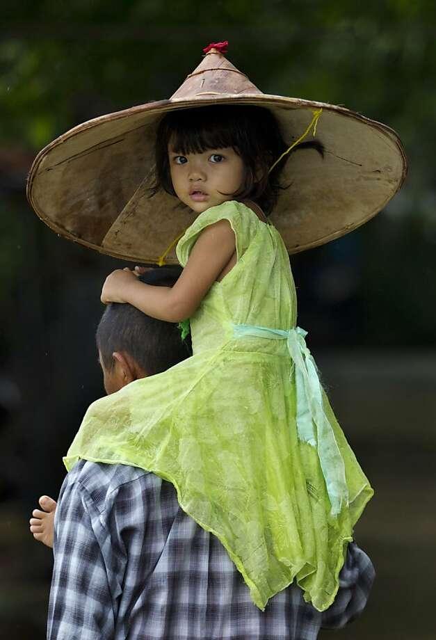 Little girl, big hat:Catching a ride in Khanaung Chaung Wa village, southeast of Yangon, Myanmar. Photo: Gemunu Amarasinghe, Associated Press