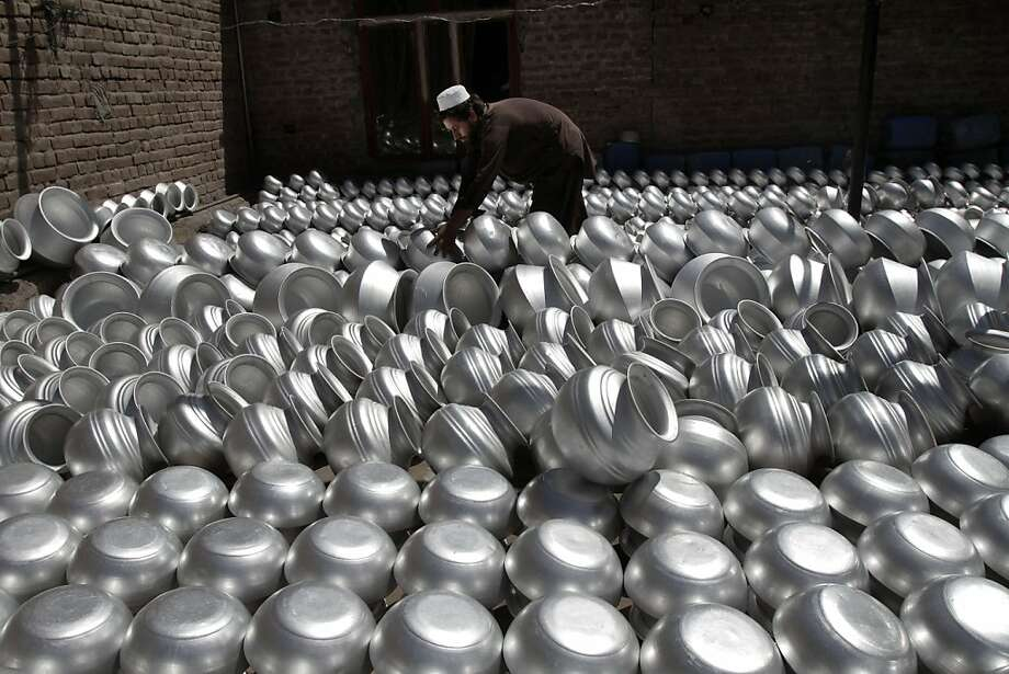 Pot and pan handler: A laborer arranges cookware at an aluminum factory in the Surkh 