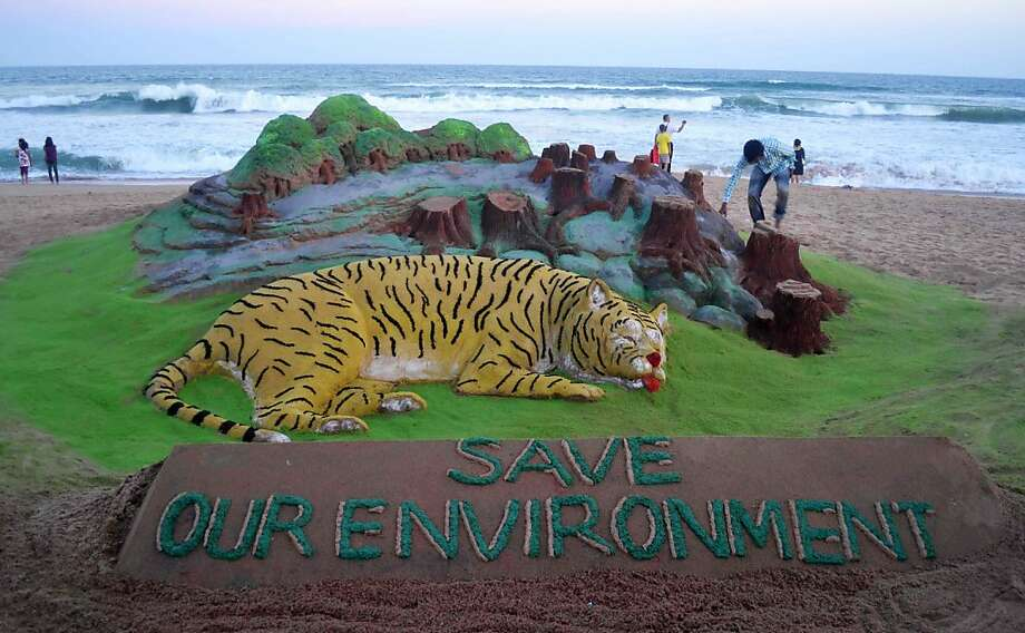 Running out of time: Sand artist Sudersan Pattnaik touches up his World Earth Day sculpture on India's Puri beach. Instead of improving with the growth of green technology and rising environmental awareness, India's cities are becoming more polluted and unhealthy, according to a new survey. Photo: Asit Kumar, AFP/Getty Images