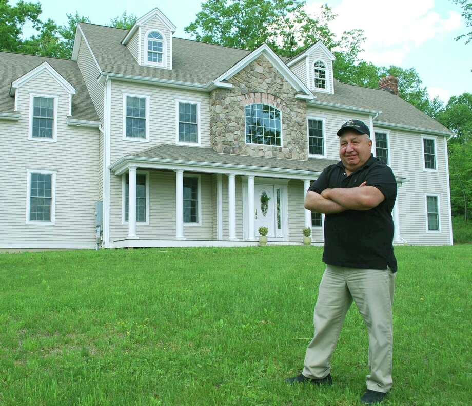Tom Pilla, owner of San-P Homes in New Milford, says his favorite part of homebuilding is benchmarking the house. Pilla, who has more than four decades in the building industry, is shown above in front of one of the houses he constructed several years ago.  For Greater New Milford Chamber of Commerce Business Quarterly, June 2013. Photo: Deborah Rose
