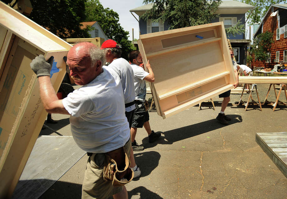 """Movie sets are carried in to a pair of houses on Ferris Street in Bridgeport, Conn. on Wednesday, June 5, 2012, where they will be filming """"And So It Goes"""", a Rob Reiner directed film starring Michael Douglas and Diane Keaton. Photo: Brian A. Pounds / Connecticut Post"""